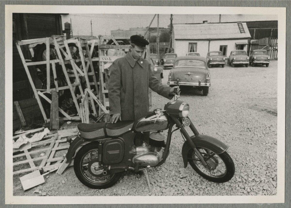 Noormees Endel uut mootorratast ostmas. Kõrval kastides mootorrattad ja taustal autoparkla sõiduautodega.