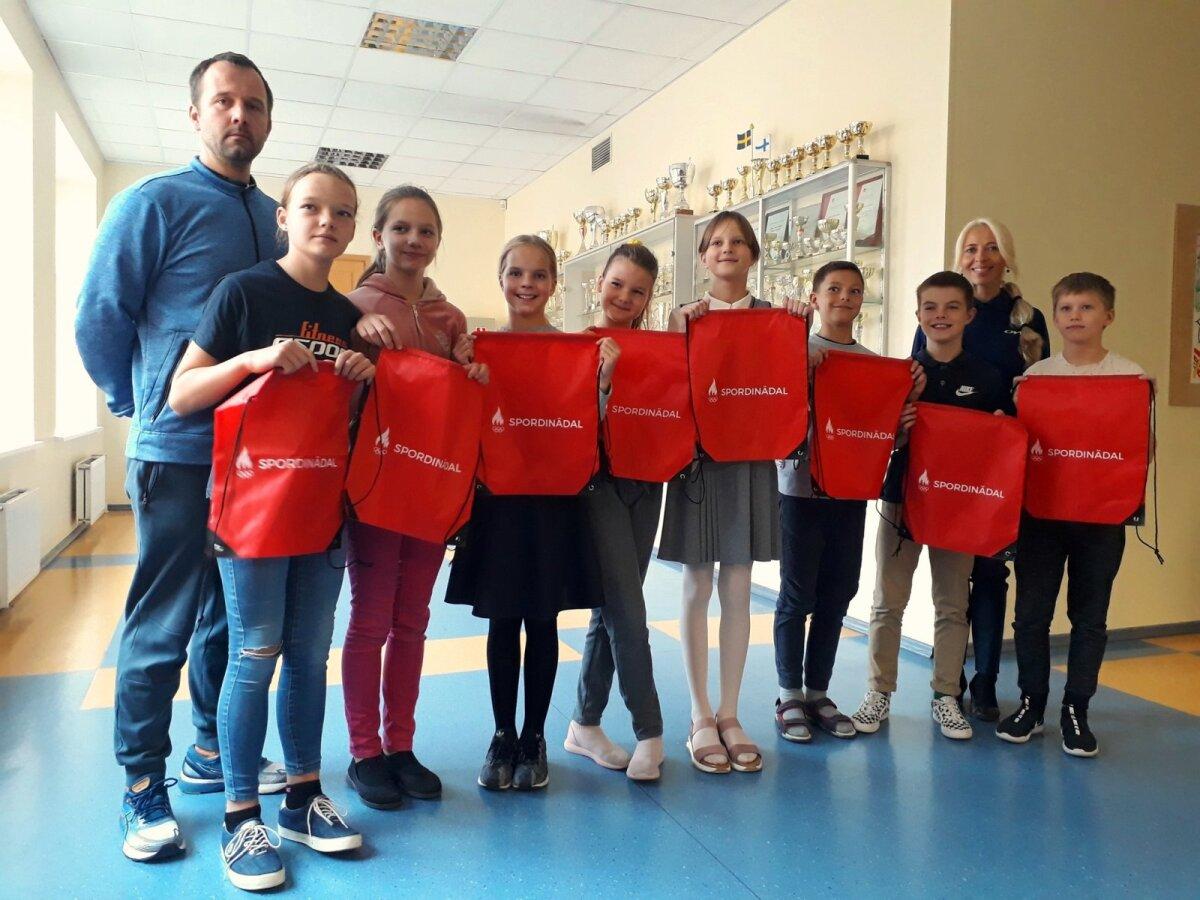 7 - 4a klassi edukaimad spordipoisid ja -tüdrukud Spordinädala autasustamisel koos õpetaja Siim Palu ja klassijuhataja Andra Puusepaga, taustaks kooli õpilaste poolt võidetud karikad