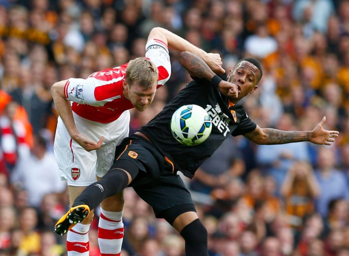 Arsenal's Per Mertesacker challenges Hull's Abel Hernandez during their English Premier League soccer match at the Emirates stadium in London