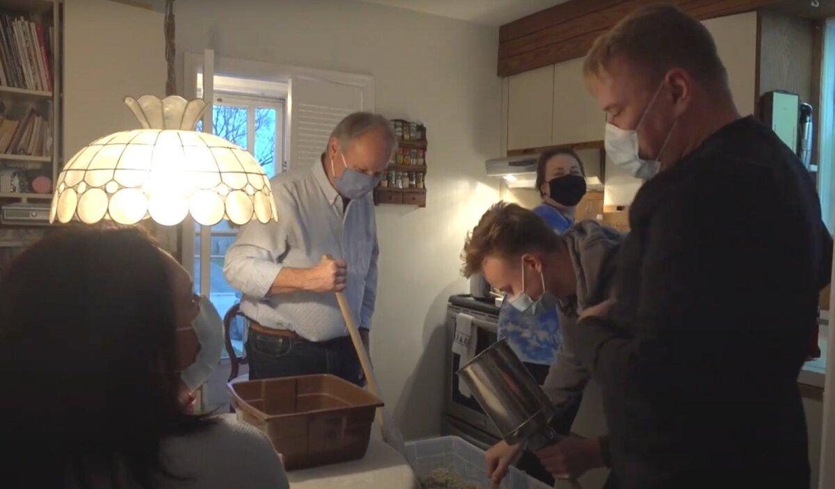 Члены семьи Лиге в Торонто делают рождественские колбаски