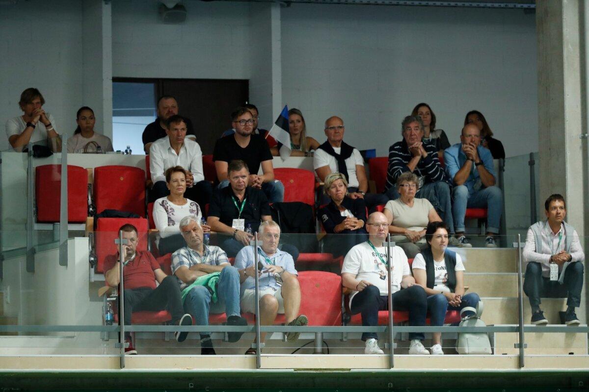 Tribüüni jagavad Urmas Sõõrumaa (ülemine rida vasakult kolmas), Guido Kangur (ülemine rida paremalt teine), nende ees hotelliärimees Tarmo Sumberg (vasakult teine) ja Anett Kontaveidi ema Ülle Milk (vasakult kolmas). Tribüüni taga on näha ka endise EOK presidendi Tiit Nuudi tütart ja Eesti naismängijat Maileen Nuudit.