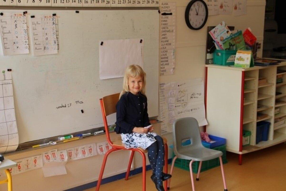 """Greta oma prantsuse koolis teistele eesti keelest rääkimas. Klass õppis temaga koos laulu """"Mu koduke on tilluke"""" ja eestikeelseid sõnu sellest: kodu, ema, isa, koerake, kiisuke, auh, näu. Koos joonistati ka Eesti lippu."""