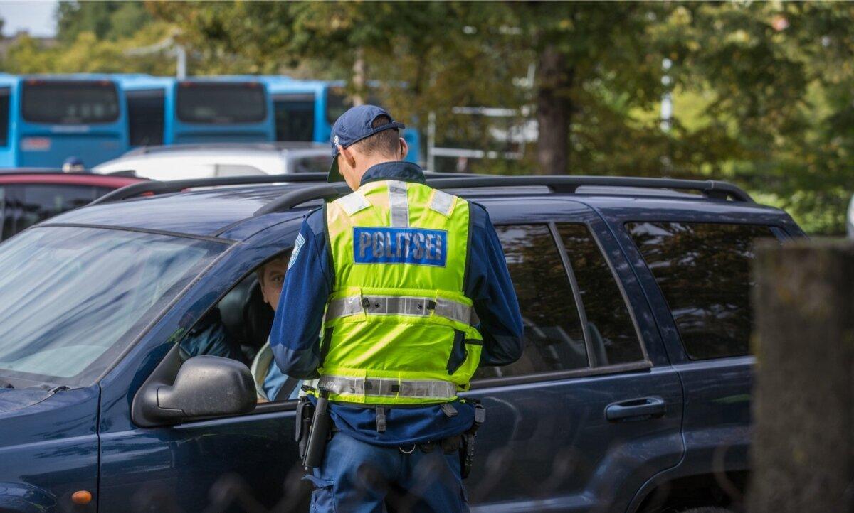 Politseinik rääkimas autojuhiga, kes alles mõni hetk tagasi liiklemise kõrval ka telefoni kasutas.