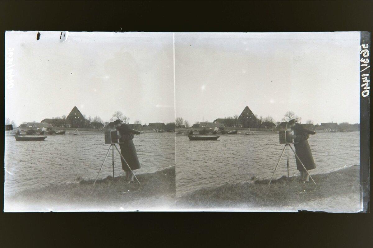 Pirita jõgi vasema kaldaga. Esiplaanil fotograaf plaatkaameraga.