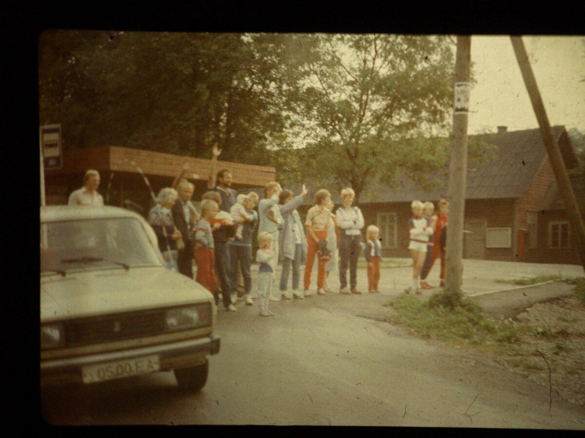 Kooliõpetaja Karin Valksaare tegi selle foto oma kodu eest minevalt teelt vaatega Karksi-Nuia poole, kus nende pere lehvitab Läti piiri poole suundujatele. Neil on meeles, kuidas miitingule sõitvad Heinz Valk ja Rein Taagepera olid poolenisti auto tagaakendest väljas ja lehvitasid rahvale. Sinna pargitud Žiguli raadiost kuulati Toompeal peetavat kõnet.
