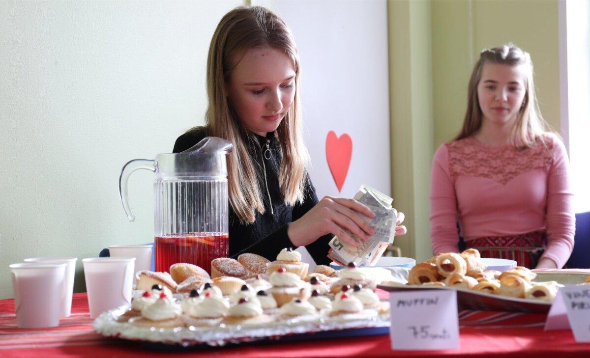 Õpilasesinduse tüdrukud müüvad ajutise kohviku leti tagant muffineid ja pirukaid.