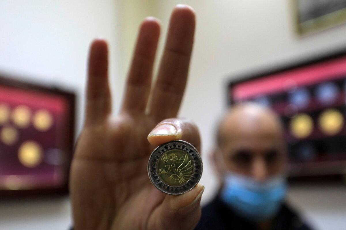 Мужчина демонстрирует монету египетского фунта в Музее монетного двора.