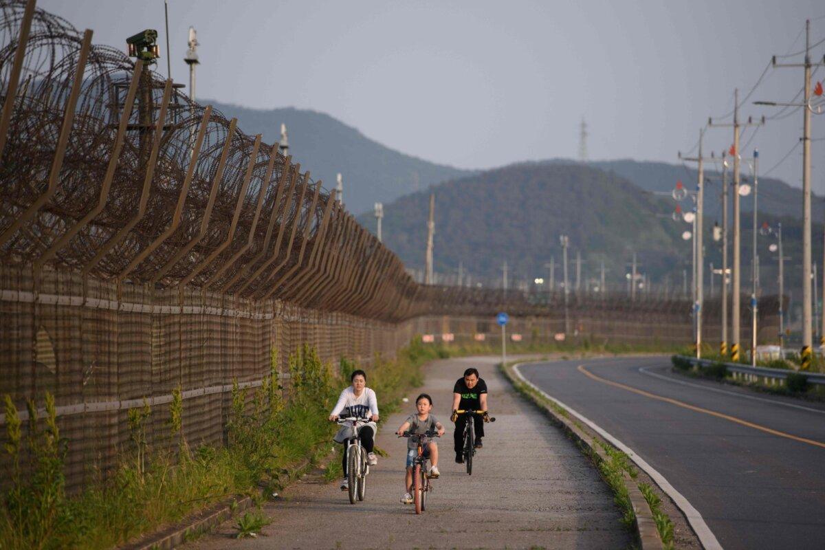 Jalgratastel pere demilitariseeritud tsooni okastraataia lähedal Lõuna-Koreas Ganghwado saarel.