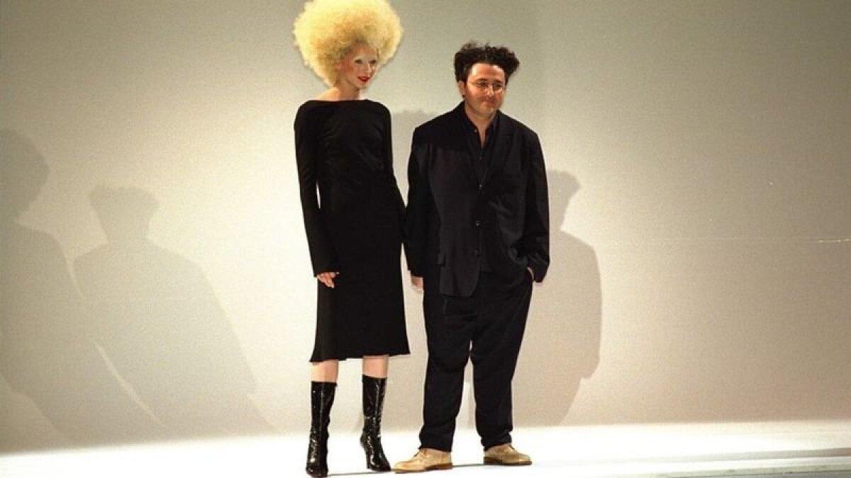 Эльбаз родился в Марокко, эмигрировал в Израиль, а в 1996 году переехал в Париж. В сезоне 1998-99 годов Эльбаз стал автором коллекции модного дома Ги Ларош.