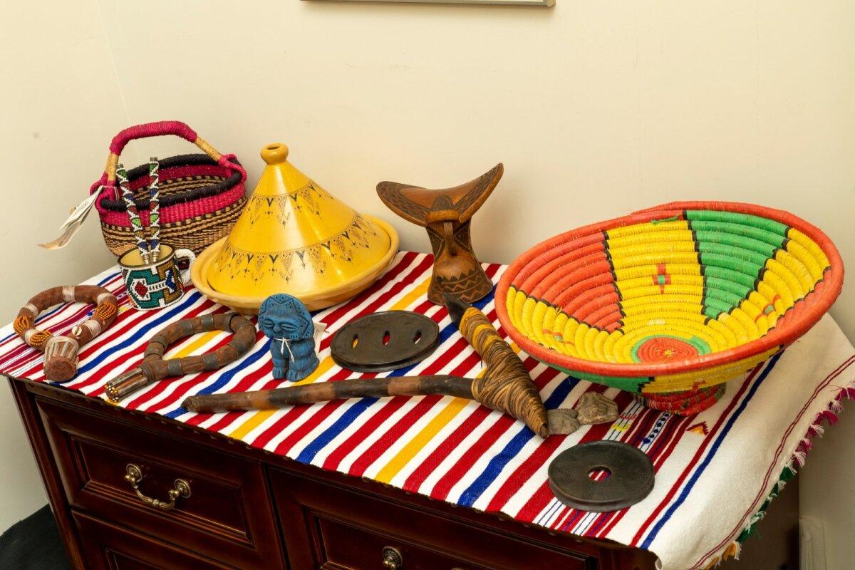 Привезенные с границы Эфиопии и Судана шейные кольца, которые в племени хамер обозначают брачный статус женщины. Темные похожие на плоскую тарелку пластины - это губные пластины  женщин племени мурси. Похожий на кирку инструмент привезли из Папуа - Новой Гвинеи, где его повседневно использовали местные.