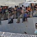 Liibüast saabunud põgenikud ootavad Itaalia rannikul sõjalaevalt maale pääsemist