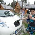 Annika Raidla näitab elektriautot, laadijaga vehib 11-aastane Sammo ja süles on seitsmekuune Jacob Georg.