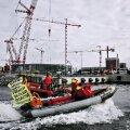 Greenpeace'i aktivistid protestivad paadiralliga Olkiluoto uue tuumareaktori vastu, mille ehitus taamalt paistab.