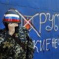 """Venemeelne sõjaväelane Slovjanskis. Tekst seina peal: """"Russ. Venelased ei alistu."""""""