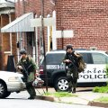 SWAT police personnel walk near a house, where a gunman suspected of killing his wife is barricaded in, in Trenton