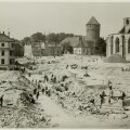 Vaade Harju tänava haljasala rajamisele. Tallinlased haljasala rajamas, tagaplaanil hooned, paremal Niguliste kiriku varemed.