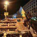 Protester carries a Ukrainian flag as he stands on barricades at Independence Square in Kiev