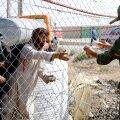 Iraani sõdur andmas afgaanile joogipoolist.