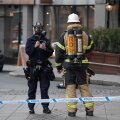 Police and rescue personnel are seen outside a company that received unidentified powder via mail, in central Stockholm