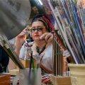Laura Šmideberga oma töötoas. Keraamilises topsis turritavad helmeste toorikud, värvilised klaaspulgad.