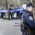 Investigators work near the body of journalist Oles Buzina in Kiev
