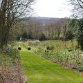 Painswick Rococo Garden. Alla tiigini viivat teed ääristavates peenardes tärkavad varsti püsililled.