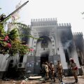 Members of the military police stand outside the burnt Rabaa Adawiya mosque, the morning after a protest camp was cleared nearby, in Cairo