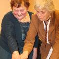 Auväärsed daamid Tiiu Elfenebein ja Maie Kork Varbola eakate ühenduse Tuluke sünnipäevatorti täpseteks lõikudeks jagamas. Ikka asjalikud, nagu alati. Foto: Piret Linnamägi
