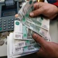 An employee counts Russian Rouble banknotes at private company's office in Krasnoyarsk
