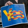 Catalunya's separatist supporters hold a sign supporting Scotland's independence as they wave Esteladas (Catalan separatist flags) at Sant Jaume square in Barcelona