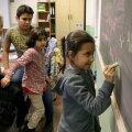 Süüria ja Afganistani põgenike lapsedBerliini koolis kirjutamist õppimas.