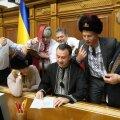 """KIRI PUTINILE: Grupp Ukraina parlamendiliikmeid kirjutamas 2018. aastal Venemaa presidendile avalikku kirja. Poliitikud tsiteerivad vene kunstniku Ilja Repini maali """"Kasakad kirjutavad Türgi sultanile"""". Väidetavasti kasutasid rahvasaadikud kunagise kasakate kirja sõnastust, pöördudes Putini kui """"Lutsiferi sekretäri"""" ning """"saatana äraneetud venna"""" poole. Rahvasaadikute naljale eelnes Venemaa sanktsioonide kehtestamine mõningatele Ukraina poliitikutele. Pildil olevad isikud on kõik sanktsioonide all."""