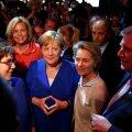 Saksa liidukantsler Angela Merkel poolehoidjatega üleeile pärast arutelu, käed kaubamärgiks saanud asendis