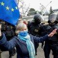 EL-i lipuga meeleavaldaja Praha Vene saatkonna ees politseiametniku kõrval. Meeleavaldused algasid, kui selgus, et 2014. aasta Vrbětice lõhkeainelao plahvatuse korraldas Venemaa luureteenistus.
