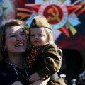 Woman and girl dressed in historical Red Army uniform wait before watching Victory Day parade to mark end of World War Two at Red Square in Moscow