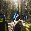 Kogukondlased lippudega Taevaskoja hiies.