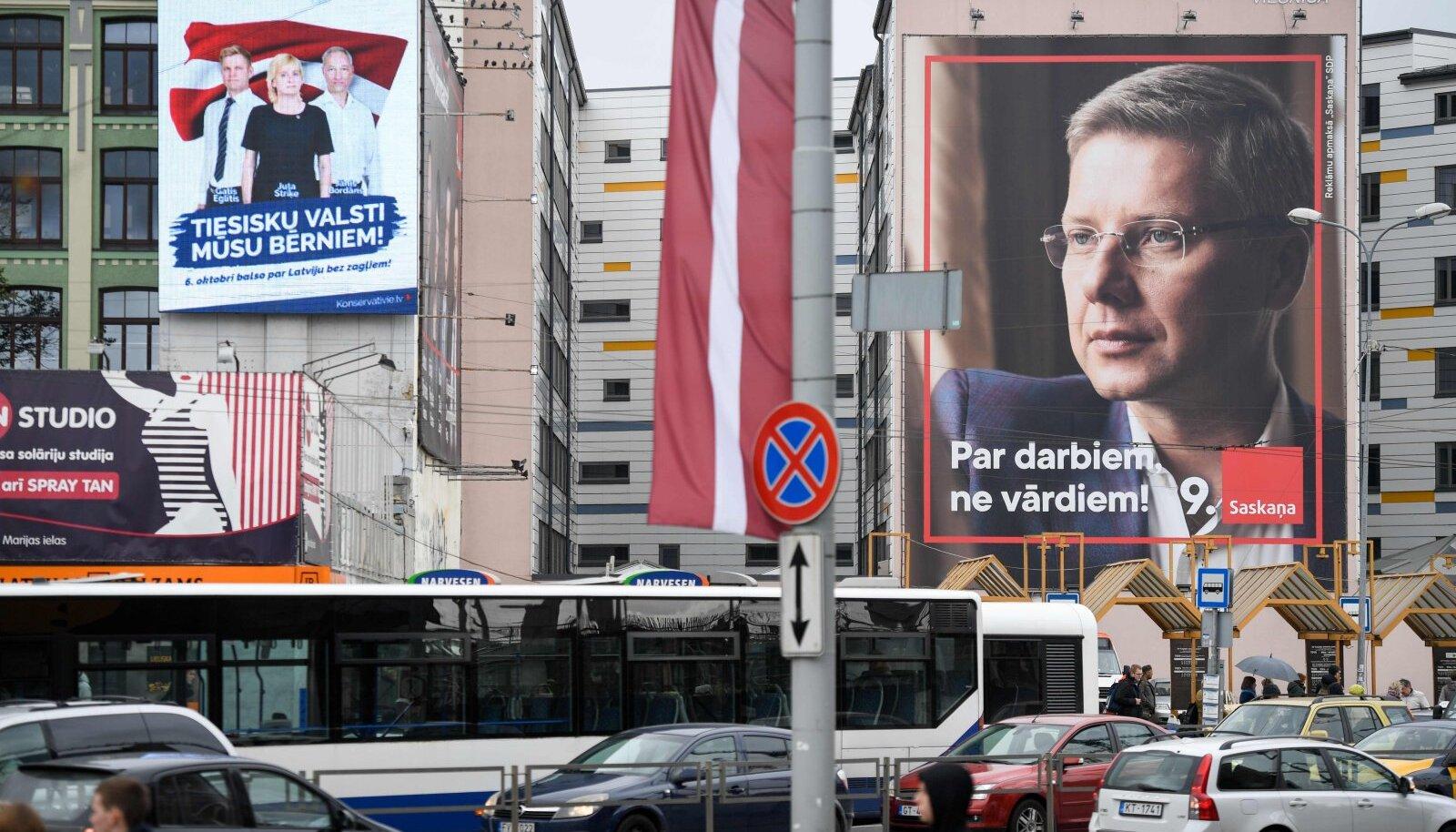 Nils Ušakovsi valimisplakat Riia busside taustal