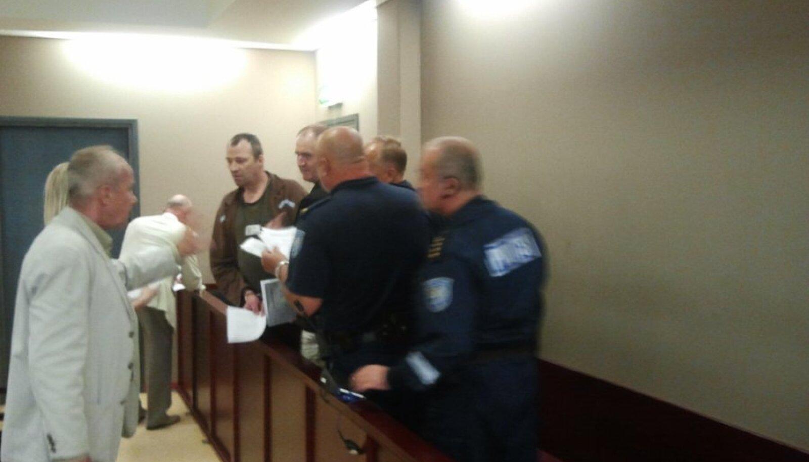 Meeste süüdimõistmine eelmisel nädalal Tartu kohtumajas. Tõkke taga on süüalused ja politseinikud, tõkke ees süüaluste kaitsjad.
