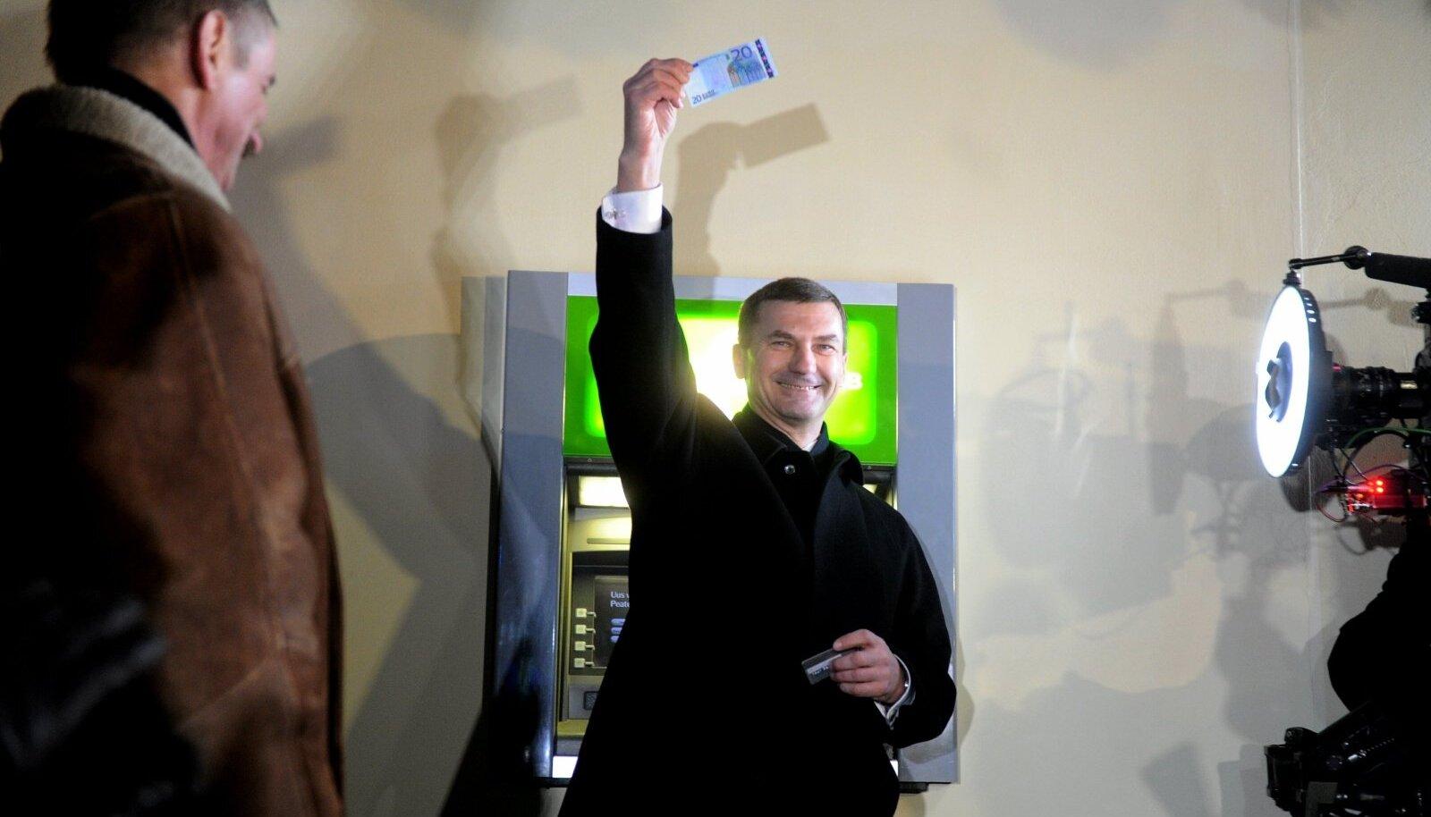 Võidukas peaminister Andrus Ansip 2011. aasta esimestel minutitel. Sularahaautomaat andis välja esimesed eurod.