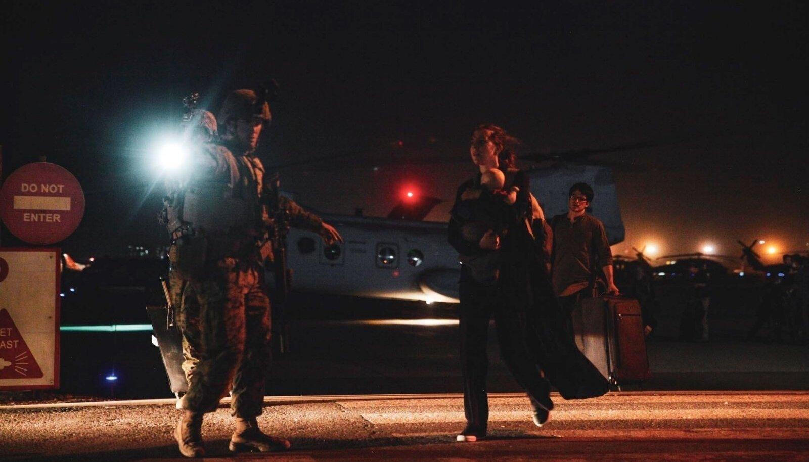 USA merejalaväelane juhatamas riigist lahkuvat Ameerika välisministeeriumi töötajat
