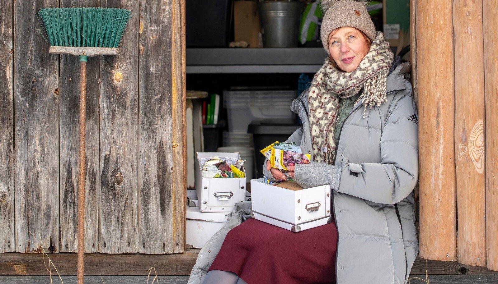 Eva Luigas istub seemnekarpidega oma armsa aiakuuri uksel.