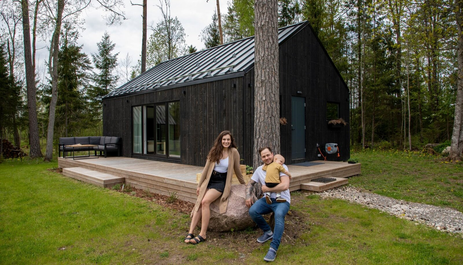 Katrin, Kristjan ja Liam oma kodu ees. Kristjan ehitas 58ruutmeetrise saunamaja valmis vaid napi kolme ja poole kuuga ja täiskohaga töö kõrvalt. Ka elumaja plaanib mees ise ehitada.