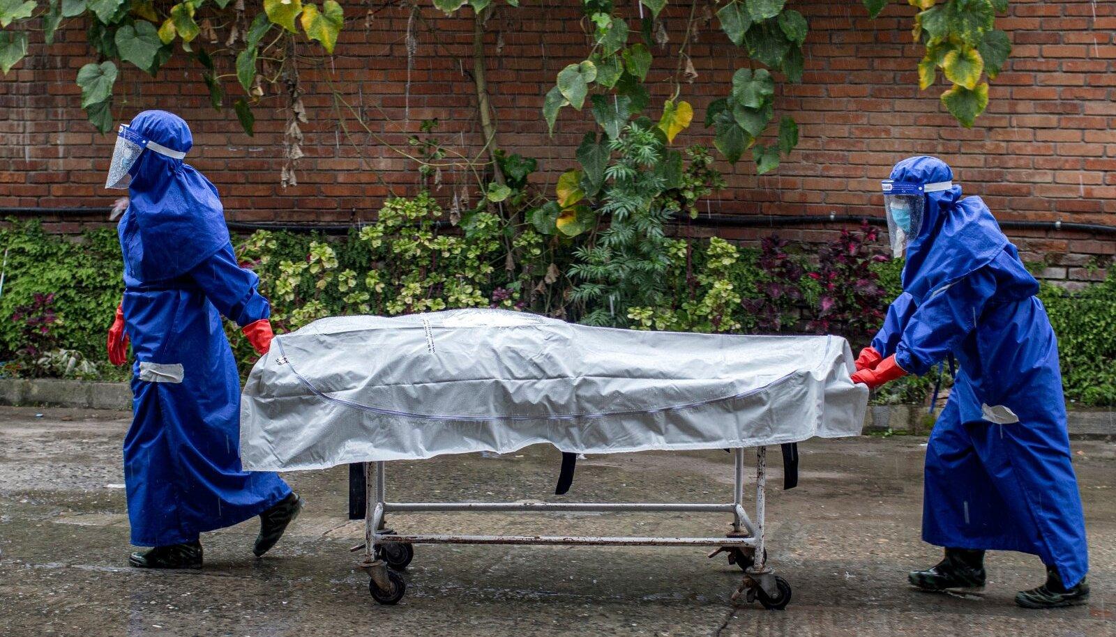 SURM, MIS VÕINUKS OLEMATA OLLA: 20. august 2020. Katmandu haigla töötajad toimetavad koroonaviiruse tagajärjel surnud inimest krematooriumisse.