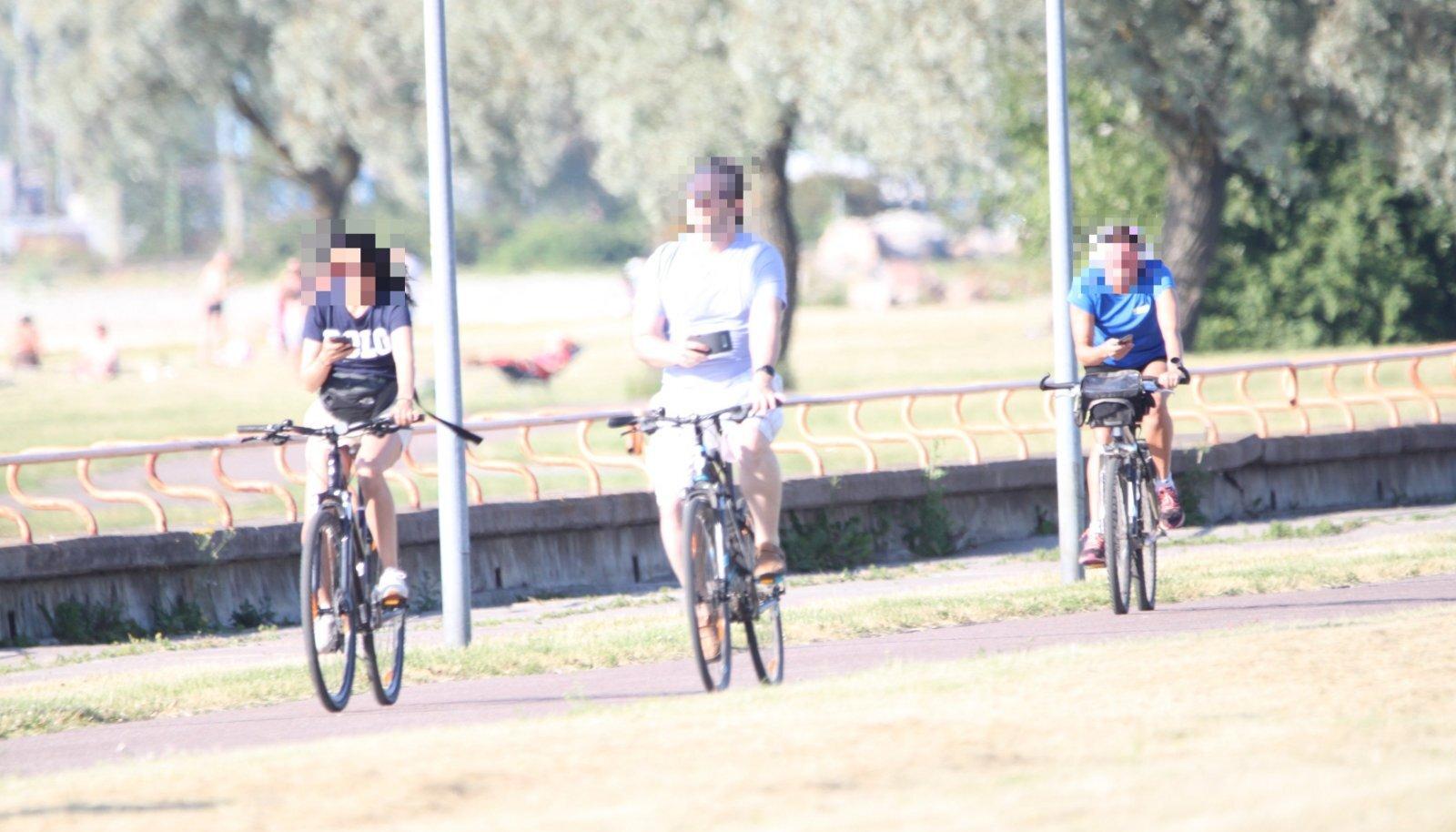 Kolm jalgratturit, kolm telefoni käes.
