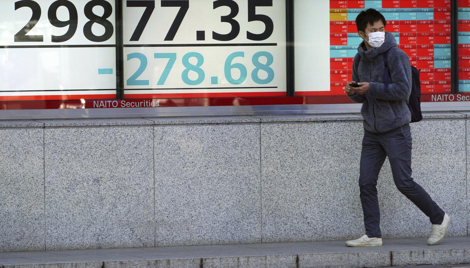 Mees möödub Tokios börsiinfo tabloost