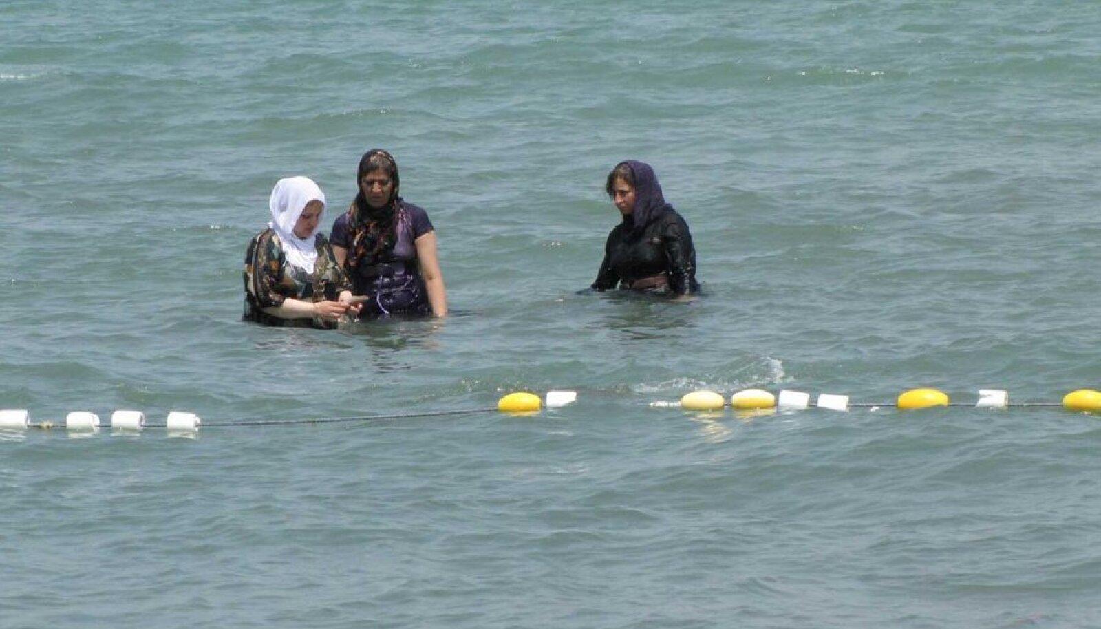 Iraani naised Kaspia meres suplemas. Noored naised püüavad karme reegleid ja nende täitmist jälgivat moraalipolitseid üha enam proovile panna. Rätid vajuvad kuklasse, musta värvi vahele seguneb erksamat, kehajooni hägustava tuunika serv tõuseb maast üha kõrgemale. Ning nelja seina vahel kantakse läänelikke rõivaid. (Foto: Kadri Ibrus)