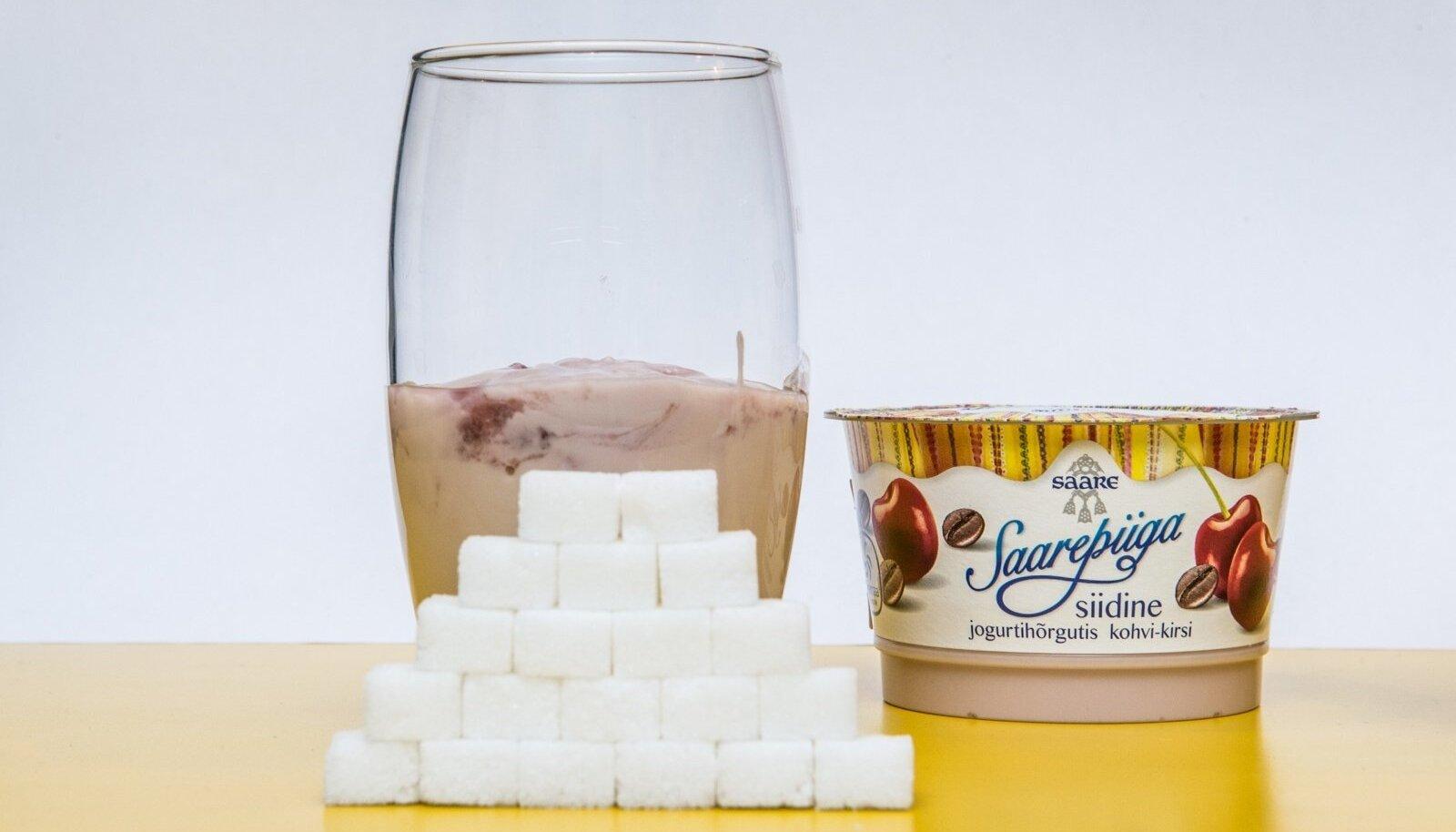 Klaasi valatud jogurtis on täpselt selline hulk suhkruid nagu kujutavad selle ees seisvad suhkrukuubikud.