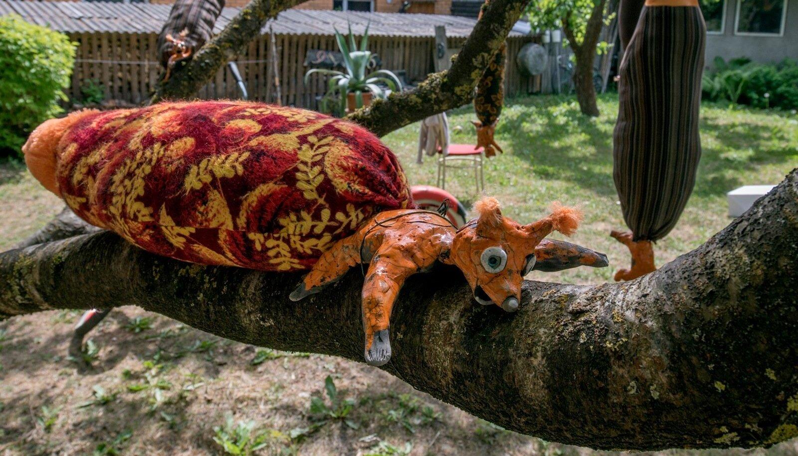Põõsast ehivad tekstiilsabaga keraamilised oravad.
