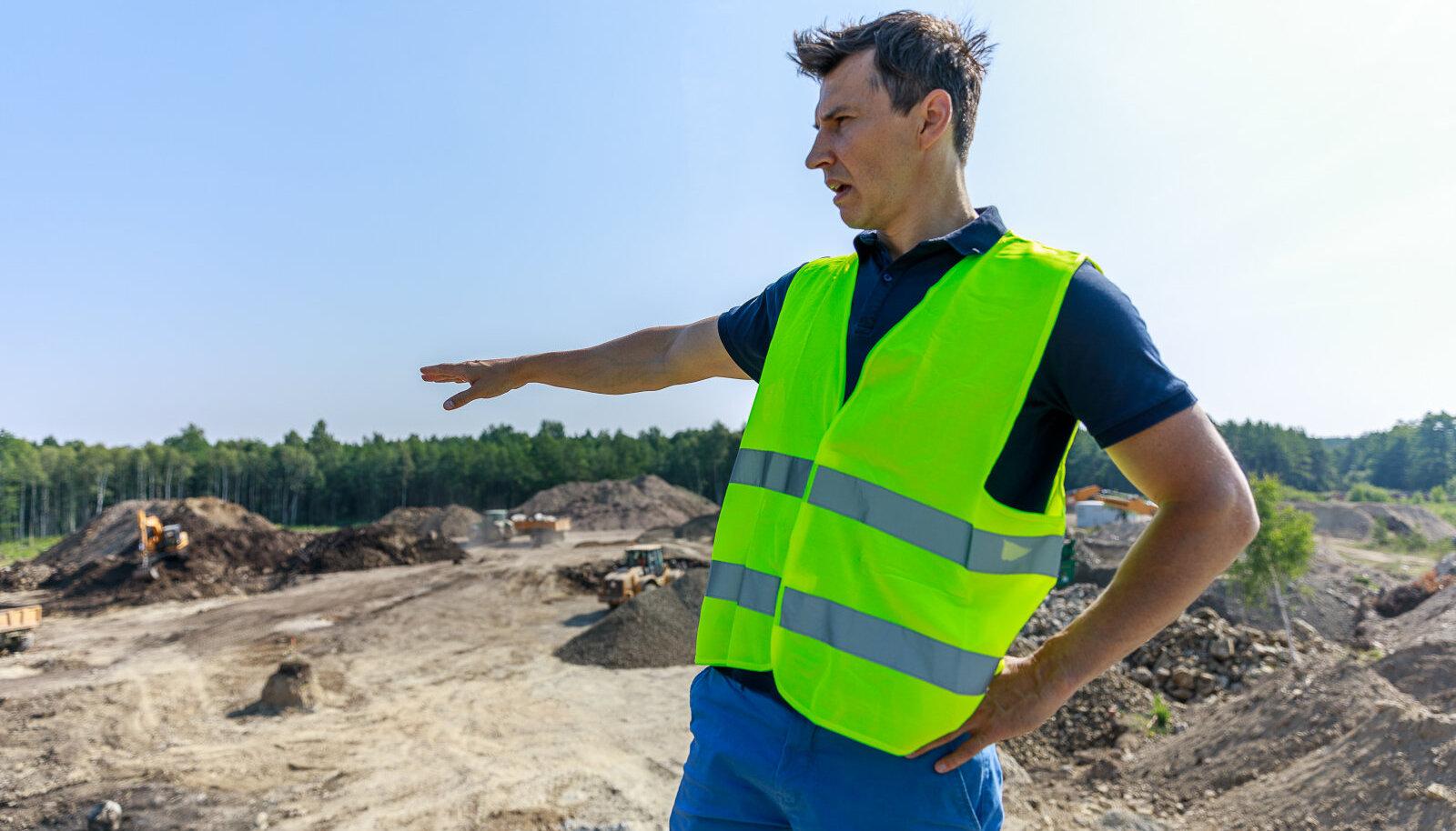 Karl Kupits osutab väljakaevatud pinnase kuhilale. Reostunud pinnas tuleb endise tehase territooriumil eemaldada kuni lubjakivist aluspõhjani.