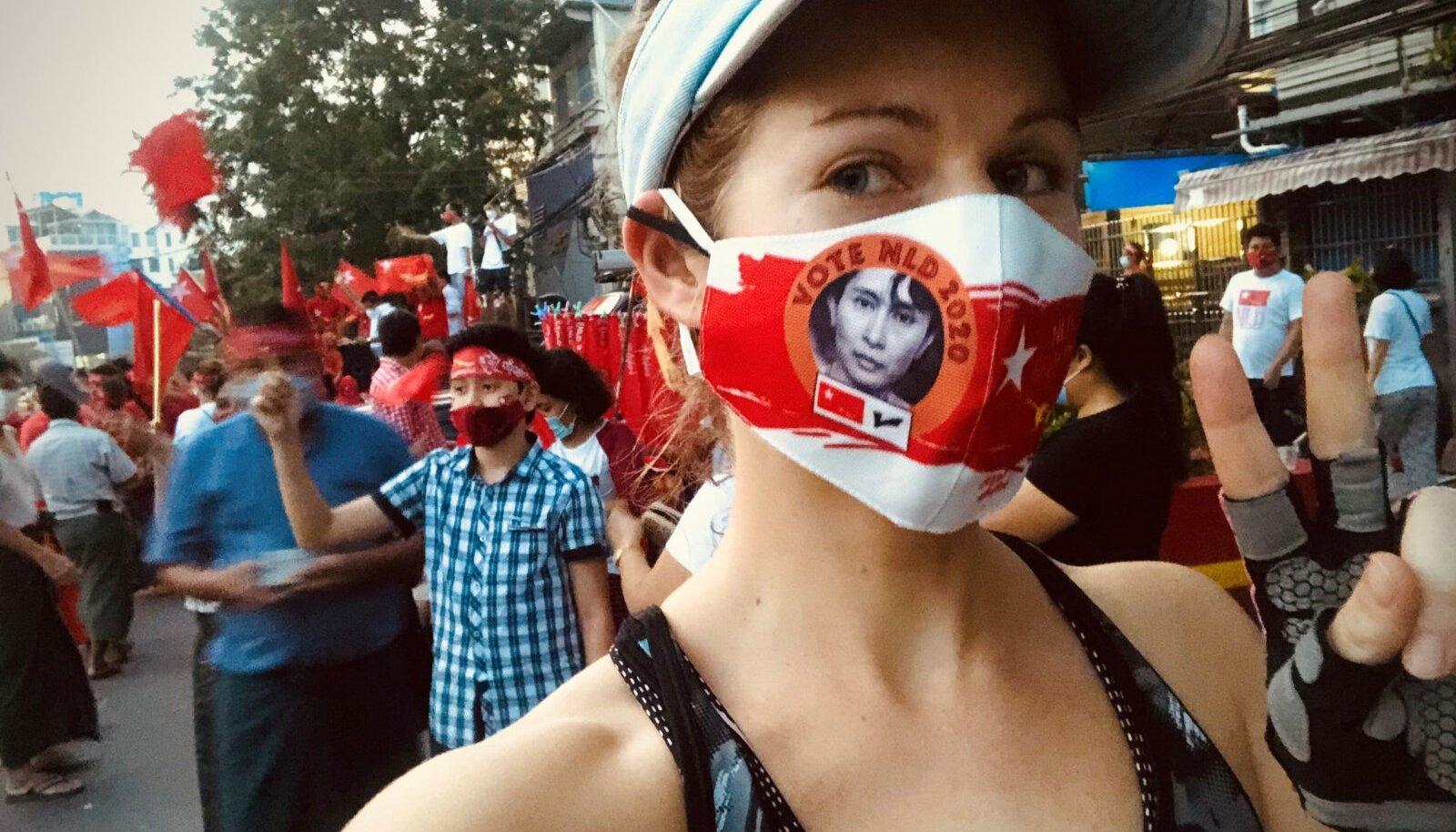 """Kõige eksootilisem maskipilt, saatjakas Helene Toivanen Myanmarist. Ta kirjutas: """"Detsembri alguses toimunud kohalike valimiste ajal levisid eriti populaarsetena valimised võitnud partei National League for Democracy (NLD) ja partei juhtfiguuri Aung San Suu Kyi näopildiga maskid. Tänavad vallutanud spontaansel valimispeol, mille keskele ma kogemata õhtul sportides sattusin, pisteti mulle ka mask kätte ja tegin endast selle päeva meenutuseks loomulikult ühe selfie. Kohalikud olid mind selle maskiga nähes vaimustuses, nii et poseerisin veel päris mitme pildi jaoks!"""""""